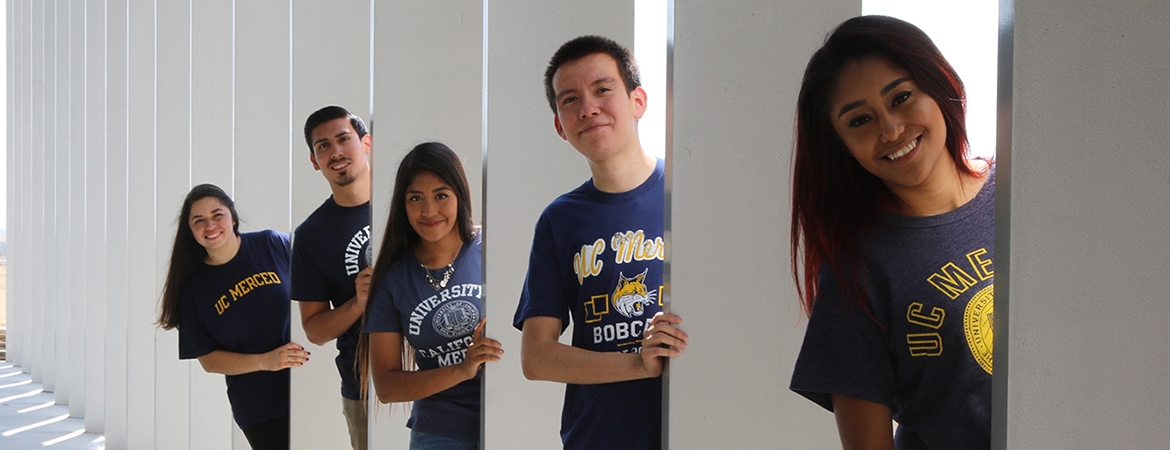 Five UC Merced students, all of them wearing the university's colors, pose near Science and Engineering 2 Building.