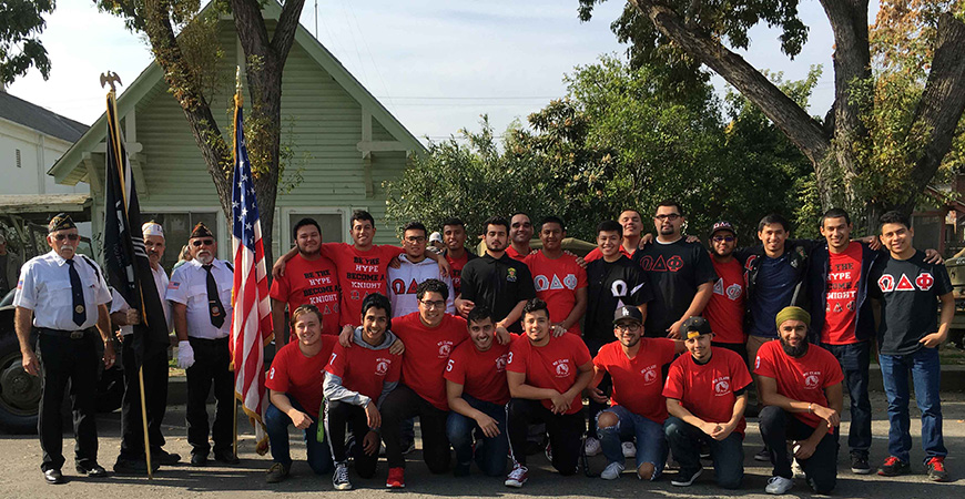 A large group of fraternity members pose in red shirts with uniformed veterans from prior world wars