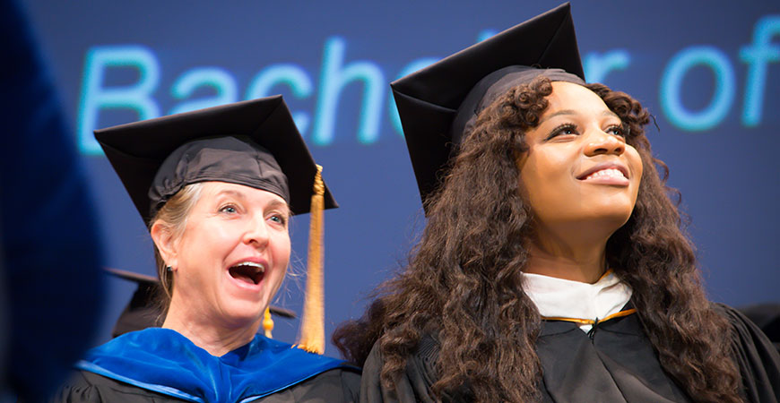 A woman seated, behind the alumna keynote speaker at fall commencement, smiles.