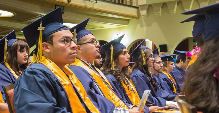Graduates seated during commencement listen to a speaker on stage.