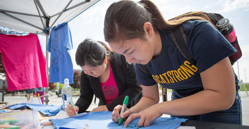 Two students decorate t-shirts for the Clothesline Project, one of many campus activities to commemorate Sexual Assault Awareness Month.
