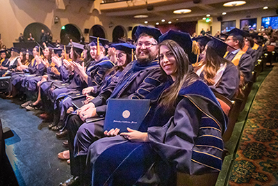 Graduate students pose after receiving their diploma.