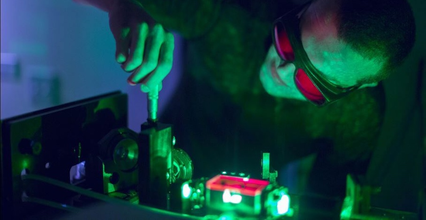 A man wearing safety goggles adjusts a laser apparatus with a screwdriver.