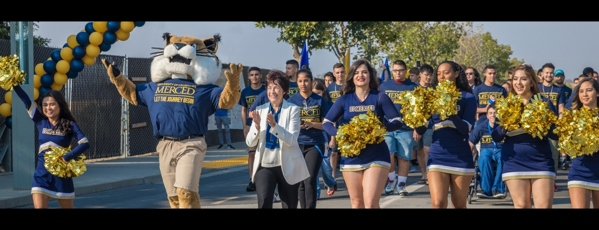 Chancellor Dorothy Leland, mascot Rufus Bobcat and the campus's cheer team lead students across Scholars Lane Bridge.